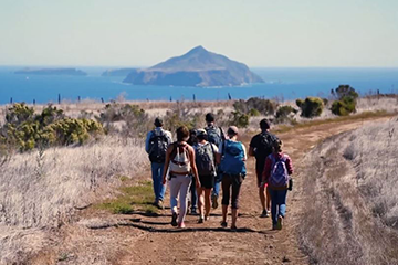 Students Walking on Path with Ocean in the Background