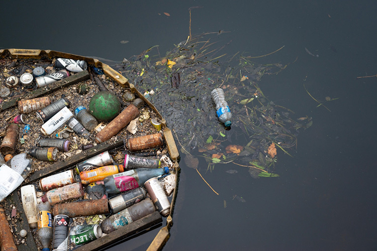 Plastic bottles and other trash collected in a river by a floating boom