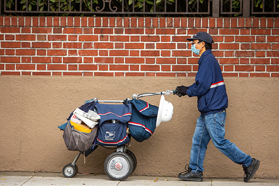 A mail carrier  wearing a surgical mask pushing his mail delivery cart.