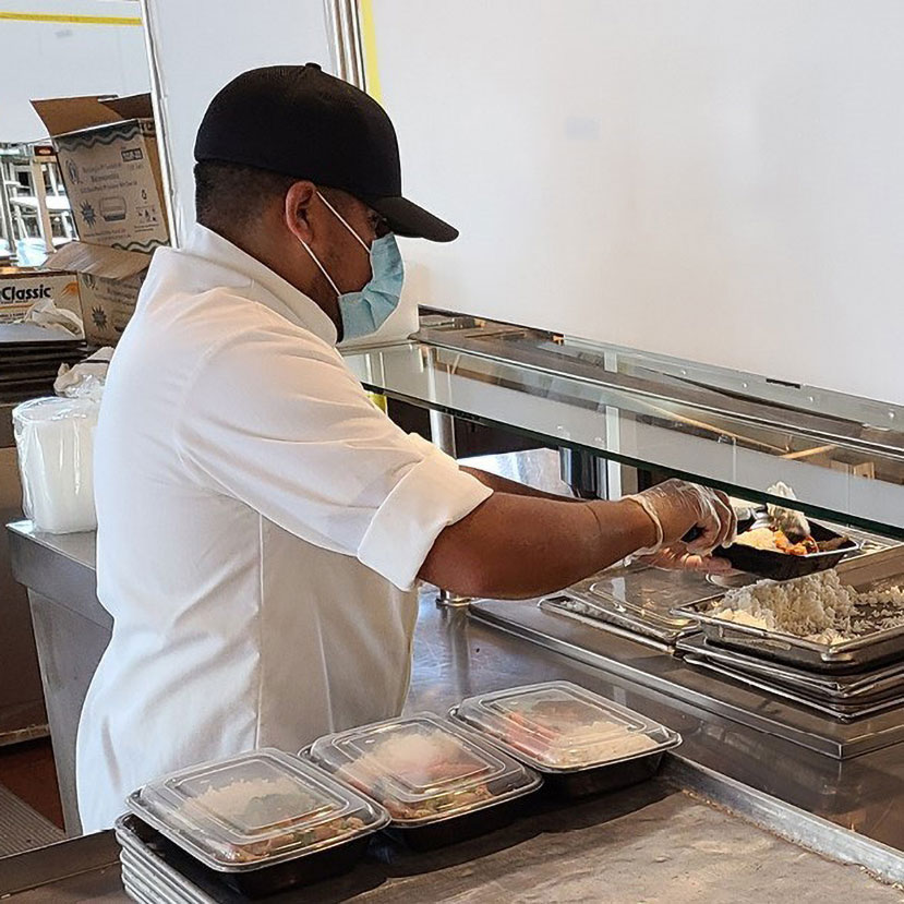 A chef preparing food in a cafeteria.