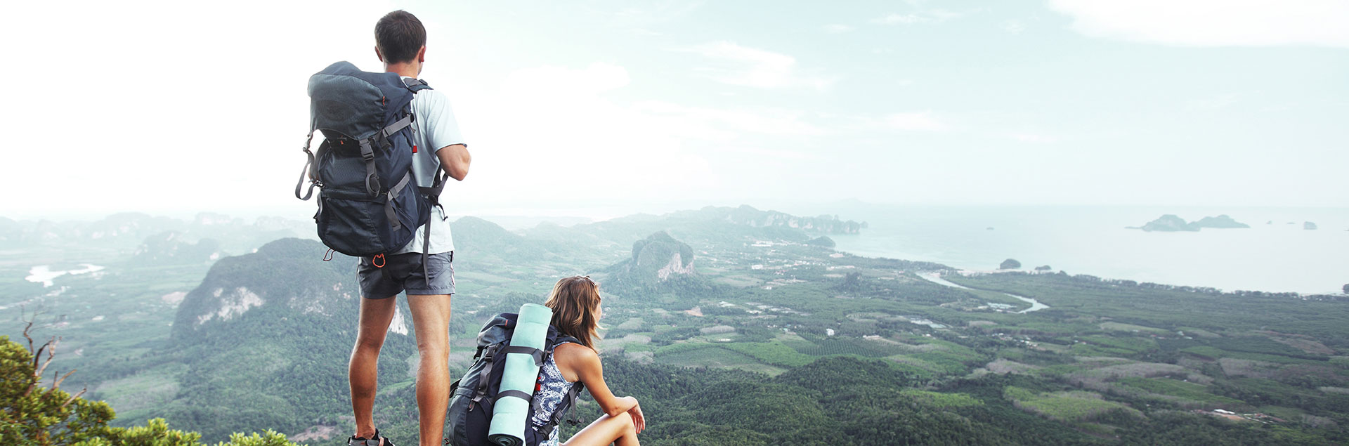 Two students on a mountain overlooking the ocean