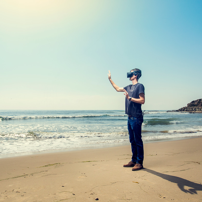 Man standing on beach wearing a virtual reality headset