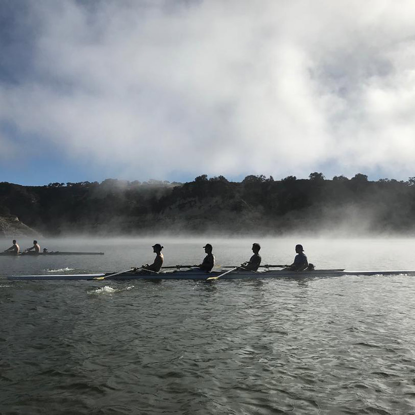 Rowing team rowing across the water through the fog