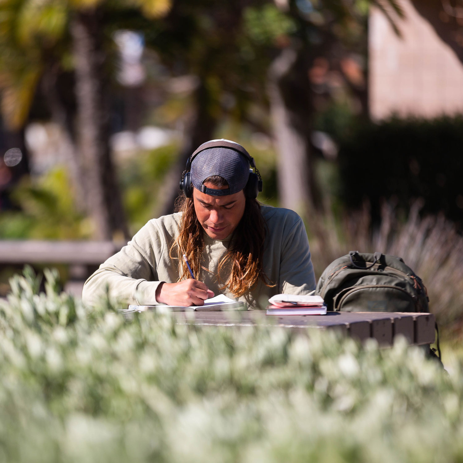 A student sitting outside in the sun writing in their notebook.