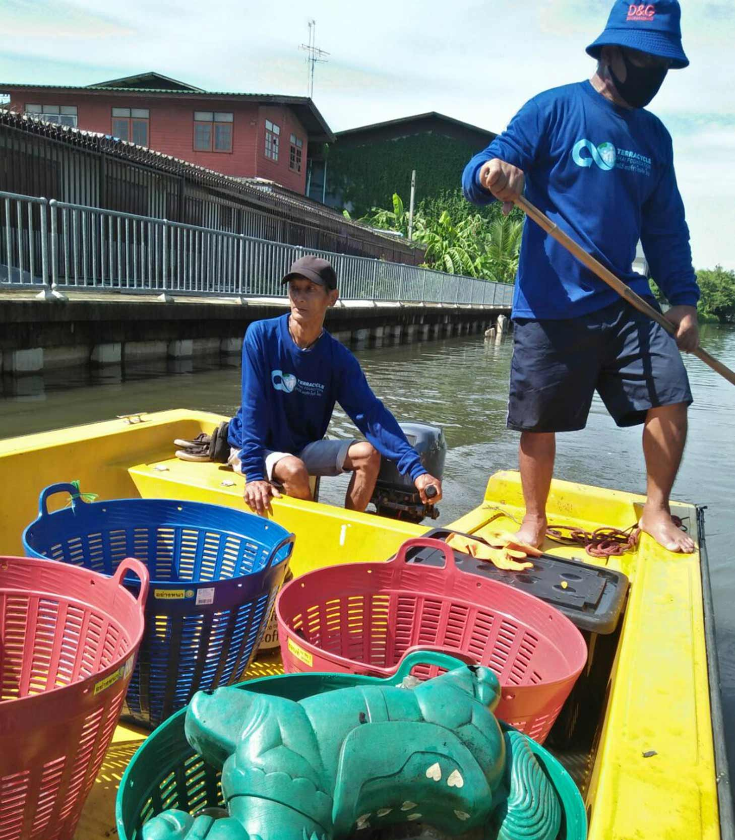 Two men collect plastic items from a river.